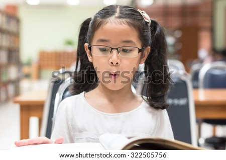 Little asian child girl wearing eyeglasses excited reading book in school library (Selective focus): Happy young female student kid looking at fairytale book with excitement in college study room    - stock photo