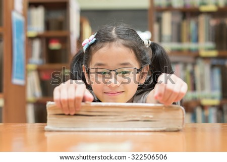Little asian child girl wearing eyeglasses relaxing reading book in school library (Selective focus): Happy young female student kid looking at big book with excitement in resource collection room     - stock photo