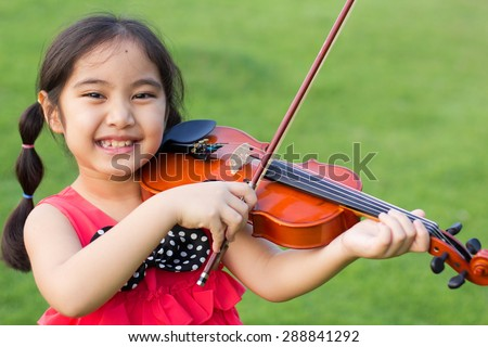Little Asian child playing violin in the park - stock photo