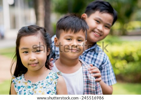 Little Asian children standing in a row and looking at the camera