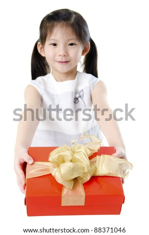 Little Asian girl arms out holding a beautiful wrapped present. Focus is on the ribbons. - stock photo
