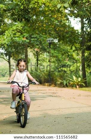 little asian girl cycling at the park in the morning - stock photo