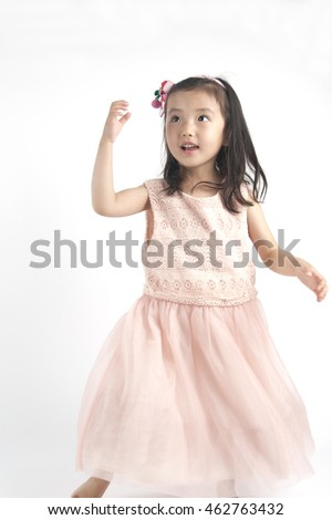 Little asian girl dancing in pink dress.