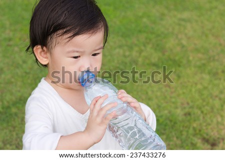 Little asian girl  drinking water from plastic bottle, after tired from a romp in the park, outdoor shot - stock photo