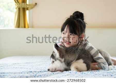 Little asian girl hugging a siberian husky puppy on bed - stock photo