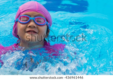Little Asian girl in swimming pool. Summer outdoor