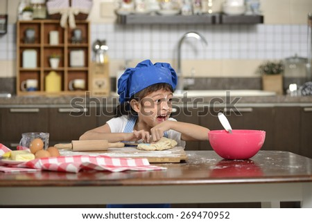 Little asian girl making dough in the kitchen - stock photo