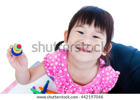 Little asian girl playing and creating toys from play dough. Child smiling and show her works from clay, over white background. Strengthen the imagination of child - stock photo