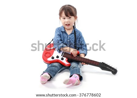 Little asian girl plays with a toy guitar on a white background