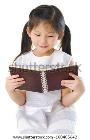 Little Asian girl reading on white background - stock photo