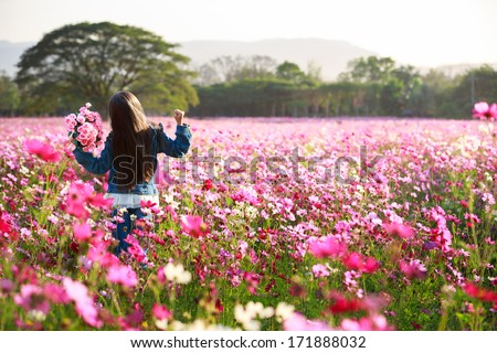 Little asian girl standing in cosmos flower fields - stock photo