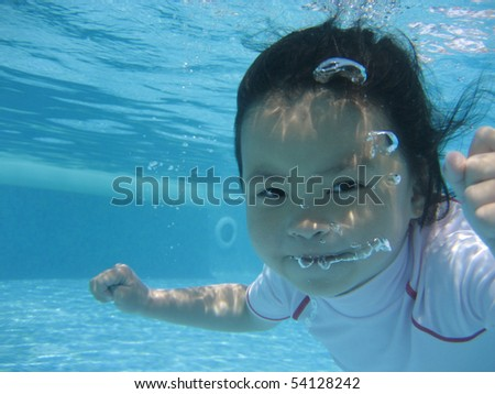 little asian girl swimming under water while looking into the camera
