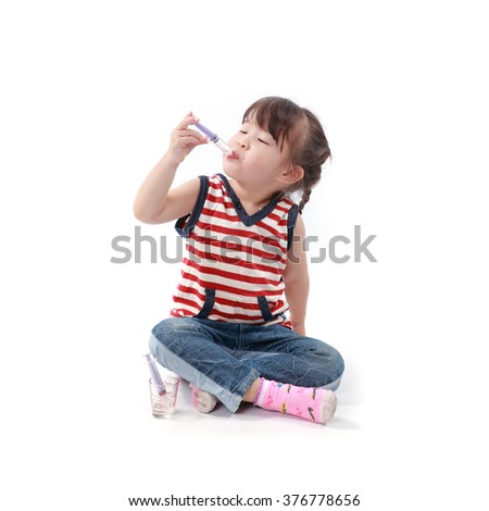 little asian girl take a medicine on white background