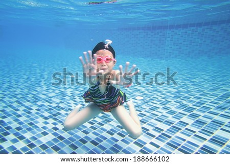 little asian girl underwater in swimming pool