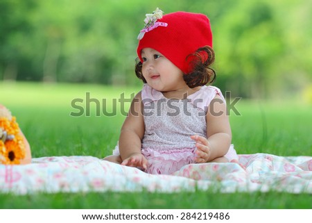 Little asian girl wearing a red hat was playing happily and smiling in the park, close up - stock photo