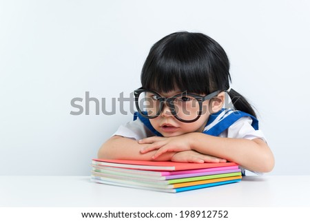 Little Asian girl wearing eyeglasses with books - stock photo