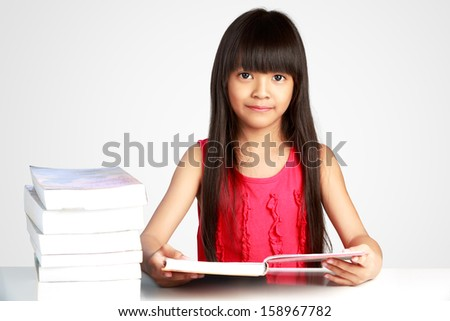 Little asian girl with books on the table, Isolated on grey background - stock photo
