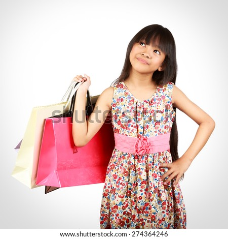 Little asian girl with colorful shopping bags - stock photo