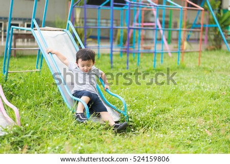 Little Asian kid playing slide at the playground under the sunlight in summer, Kids play on school yard. Happy kid in kindergarten, color tone, shallow DOF