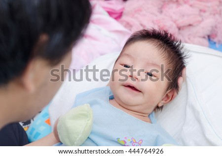 Little asian newborn on his father hand