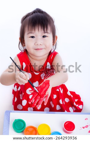 Little asian (thai) child happily, pretty girl looking at the camera, smiling and painting her hand using multicolored drawing tools on white background, creativity and education concepts. Studio shot - stock photo