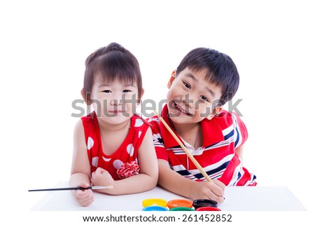 Little asian (thai) children happily, brother and sister looking at the camera and smiling, holding a paintbrush, Concepts of creativity and education. Isolated on white background. Studio shot - stock photo