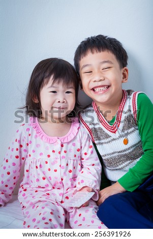 Little asian (thai) children happily, brother and sister smiling, conceptual image about loving and bonding of sibling - stock photo