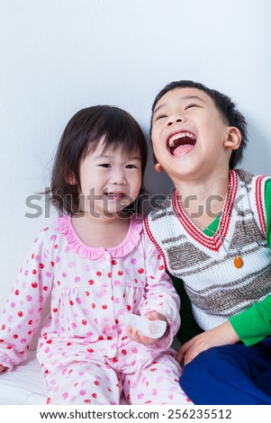 Little asian (thai) children happily, brother laughing and sister smiling on white wall background, conceptual image about loving and bonding of sibling - stock photo
