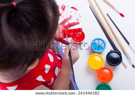 Little asian (thai) girl painting her palms using multicolored drawing instruments (watercolor paints, paintbrush), creativity concept, studio shot, top view - stock photo
