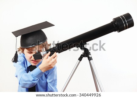 Little astronomer in academic hat looking through a telescope on a white background - stock photo