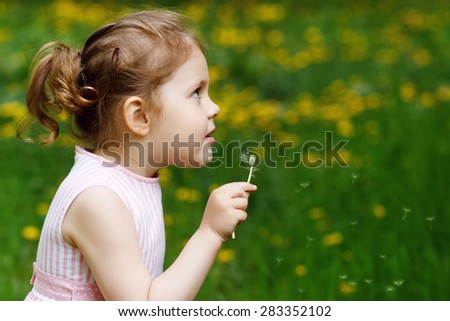 Little attractive girl in the field with dandelions, blowing dandelions. Rest, play, childhood