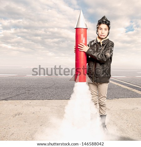 little aviator holding a rocket at the airport - stock photo