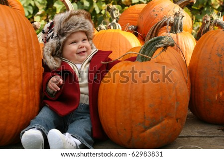 Little baby amongst pumpkins - stock photo