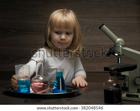 Little baby and chemical experiments. Chemical vessels. Home Laboratory. Child mixes colored liquid. Microscope