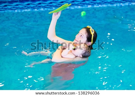Little baby and her mother relaxing in the swimming pool - stock photo