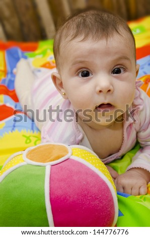 Little baby and toy balll - stock photo