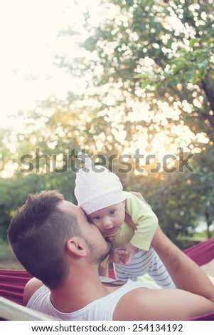 little baby and young father on backyard - stock photo