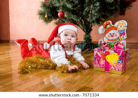 Little baby as Santa in red cap laying on the floor with gifts #4