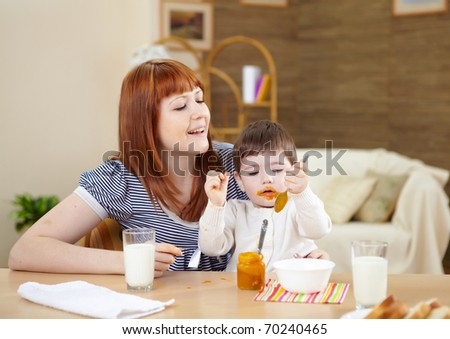 little baby at home sitting at the table and having meal - stock photo