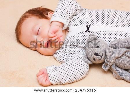 Little baby boy calmly sleeping with his teddybear. - stock photo