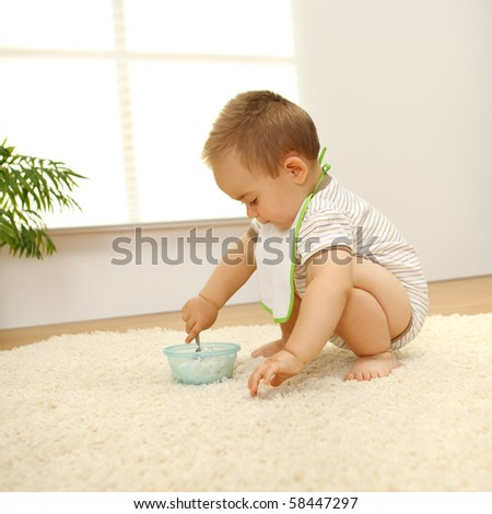 Little baby boy eating alone on white carpet