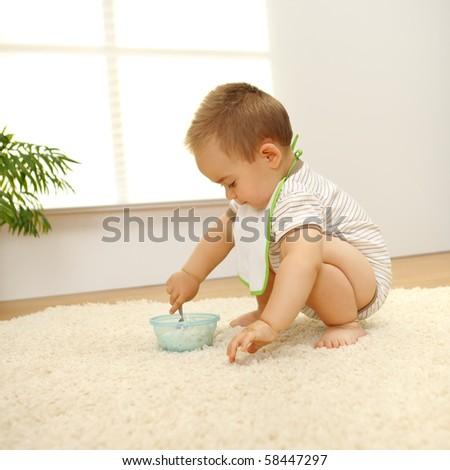 Little baby boy eating alone on white carpet - stock photo