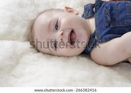 little baby boy  having fun lying on his back - stock photo
