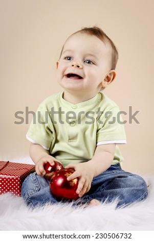 Little baby boy holding christmas balls - stock photo