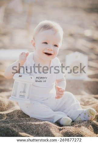 Little baby-boy in a cute suit sitting on a sand at the beach with white lantern. Cute blue flags on the background - stock photo