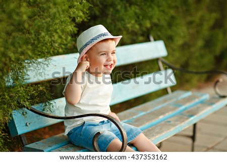 Little baby boy in a hat sitting on a bench in the summer and cheerfully laughs - stock photo