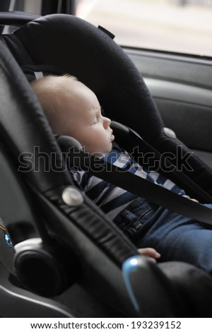 Little baby boy in car seat  - stock photo