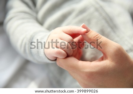Little baby boy in grey pajamas holding mother's hand on the bed, close up