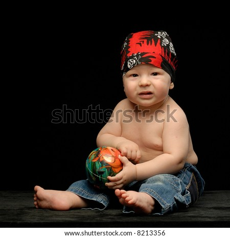 Little baby boy in sculled bandana with small ball next to black cap - stock photo
