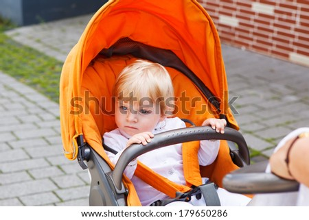 Little baby boy in white christening gown clothes sitting in orange stroller - stock photo